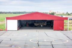 Helipad och öppen hangar med en helikopter Royaltyfria Foton