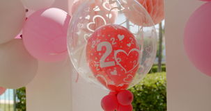 Helium balloons celebrating a two year anniversary. Decorative pink and red helium balloons with heart shapes celebrating with joy a two year anniversary stock footage
