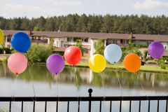 Helium baloons at bridge with lake and houses  Royalty Free Stock Photos