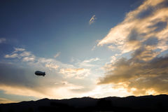 Helium blimp advertising ballon floating sunset sky and mountain. Background stock image