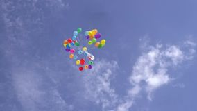 Helium inflated balloons fly in the sky Royalty Free Stock Image