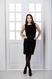 Hellång klänning för svart för modemodell som bakom poserar i dörrar för studiovindhemmiljö Royaltyfri Fotografi