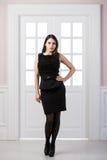 Hellång klänning för svart för modemodell som bakom poserar i dörrar för studiovindhemmiljö Royaltyfri Foto