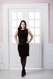 Hellång klänning för svart för modemodell som bakom poserar i dörrar för studiovindhemmiljö Arkivbilder