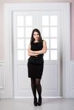 Hellång klänning för svart för modemodell som bakom poserar i dörrar för studiovindhemmiljö Arkivbild