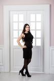 Hellång klänning för svart för modemodell som bakom poserar i dörrar för studiovindhemmiljö Fotografering för Bildbyråer