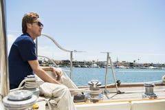 Hellång sidosikt av mansammanträde på yachten fotografering för bildbyråer
