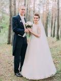Hellång sikt av de gladlynta nygift personparen som rymmer bröllopbuketten i skogen arkivbild