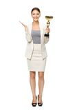 Hellång stående av affärskvinnan med den guld- koppen arkivfoto