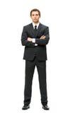 Hellång stående av affärsmannen med korsade händer arkivfoto