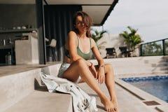 Hellång stående av den attraktiva moderna flickan som sitter på trappa nära pölen i modern villa i solsken royaltyfri bild
