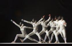 Hellång stående av den bärande vita fäktningdräkten för kvinna på svart Arkivbilder
