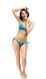 Hellång stående av den kvinnliga bärande bikinin arkivfoton