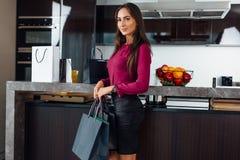 Hellång stående av den unga stilfulla kvinnan med shoppingpåsar som står i köket arkivbild