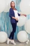 Hellång stående av den upprymda gravida kvinnan som poserar i studio s Royaltyfri Fotografi
