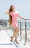 Hellång stående av en attraktiv blond kvinna med långt rakt blont hår i en rosa klänning lång modell för modehår arkivbild