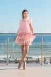 Hellång stående av en charmig kvinna i en rosa klänning med ruches på bakgrunden av ett hav Strand, hav och sommarbegrepp royaltyfri bild
