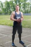Hellång stående av en ung amerikansk fotbollsspelare med en boll royaltyfri foto