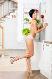 Hellång stående av kvinnan nära det öppnade kylskåp Royaltyfria Foton