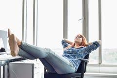 Hellångt av affärskvinnan som kopplar av med fot upp på skrivbordet i idérikt kontor Royaltyfria Bilder