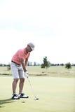 Hellångt av den medelåldersa mannen som spelar golf på kursen Royaltyfri Foto