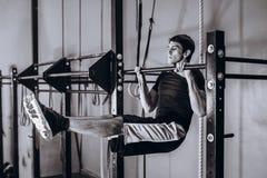Hellångt av den starka mannen som gör handtag-upp på på en tvärbom - hängande Abs för horisontalstång Arkivbilder