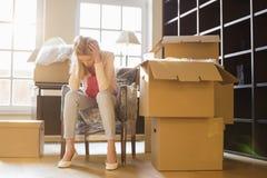 Hellångt av frustrerat kvinnasammanträde vid kartonger i nytt hus royaltyfria foton