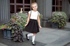 Hell?ngt av lite att le flickan i skolalikformign som poserar mot en skolaing?ngsbakgrund arkivbild