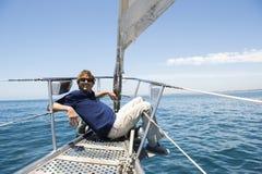 Hellångt av lyckligt mansammanträde på pilbåge av yachten arkivfoton