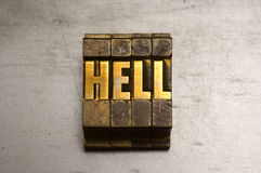 Hell. Brass / Gold colored Hell on silver metal background royalty free stock image