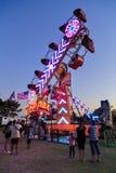 Hell belichtete 'Reißverschluss'Fahrt am Sommerkarneval, fotografiert nachts stockfotografie