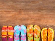Hell farbige Flipflops auf Holz Stockfotos
