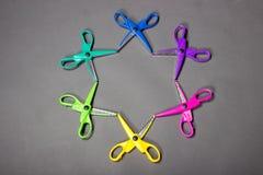Hell farbiges Handwerk scissors das Legen auf einen grauen Hintergrund in Form eines Sternes lizenzfreie stockbilder
