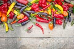 Hell farbiges Misch-Chillis auf verwittertem Holztisch Lizenzfreie Stockbilder