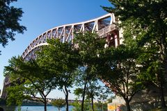 Hell Gate Bridge over the river and trees with blue sky at Astoria park Royalty Free Stock Images