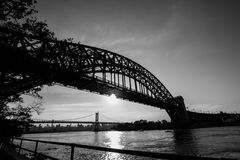 The Hell Gate Bridge and the sun reflect on the river in black and white style Royalty Free Stock Photography