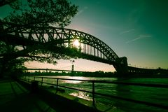 The Hell Gate Bridge and Triborough bridge over the river with walkway and the sun in dark green vintage style Royalty Free Stock Image