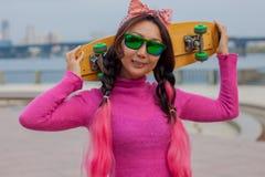 Hell gekleidetes Mädchen mit Skateboard in der Stadt stockbilder