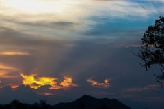 Hell in Heaven colorful Clouds Silhouette blue Sky Background Evening golden sunset with rays of light shining through clouds. Stock Image