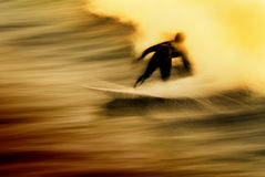 Hell Ride. Long exposure of a surfer at sunset. Has a grunge like feel with the rider appearing to ride out of flames stock images