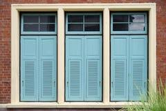 Hellblaue Kombinationsfenster auf Backsteinmauer Stockfotos
