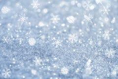 Hellblaue Schneeflocken und Funkelnscheine Stockfoto