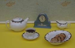 Hellblaue Wedgwood-Uhr, Jasperware, mit angewandter Entlastungsplatte des weißen Lehms, nahe bei einem englischen teaset und eine lizenzfreie stockfotografie