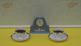 Hellblaue Wedgwood-Uhr, Jasperware, mit angewandter Entlastungsplatte des weißen Lehms, nahe bei englischen Teetassen und Unterta stockfotografie