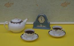 Hellblaue Wedgwood-Uhr, Jasperware, mit angewandter Entlastungsplatte des weißen Lehms, nahe bei englischen Teetassen und Unterta lizenzfreie stockbilder