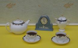 Hellblaue Wedgwood-Uhr Jasperware mit angewandter Entlastungsplatte des weißen Lehms nahe bei Teetassen und Untertassen-, Teekann lizenzfreie stockfotos