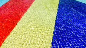 Hellblauer, roter, gelber und blauer gestreifter Mosaikfußboden des Brunnens bedeckt mit Wasser Stockfoto