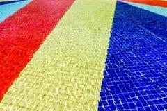 Hellblauer, roter, gelber und blauer gestreifter Mosaikfußboden des Brunnens bedeckt mit Wasser Stockfotos