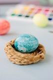Hellblaues Farb-Osterei auf Nest über hellem Hintergrund Lizenzfreie Stockfotografie