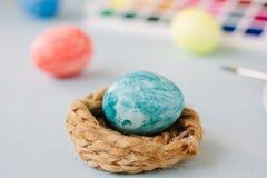 Hellblaues Farb-Osterei auf Nest über hellem Hintergrund Lizenzfreie Stockfotos